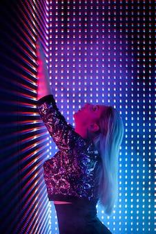 Mode jeune femme élégante. fond de néon coloré, tourné en studio.