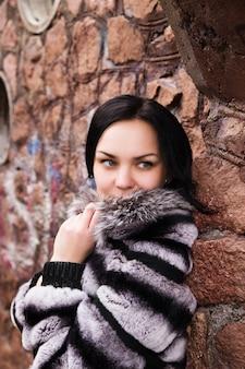 Mode jeune femme élégante en robe blanche et manteau de fourrure au mur de briques