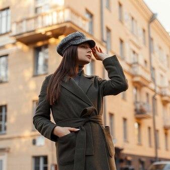 Mode jeune femme européenne avec un chapeau élégant et un manteau vintage à la mode marchant dans la rue de la ville