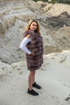 Mode jeune femme en manteau de fourrure posant sur des rochers de sable
