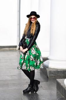 Mode jeune femme marchant dans la rue avec veste en cuir et jupe à fleurs