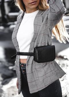 Mode jeune femme portant un chapeau noir veste manteau à carreaux sac à main