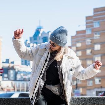 À la mode jeune femme portant un chapeau en tricot bleu qui danse dans la ville