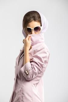 Mode jeune femme posant portant un manteau rose et des lunettes de soleil blanches