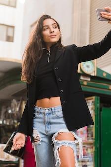À la mode jeune femme prenant selfie sur un téléphone intelligent en plein air