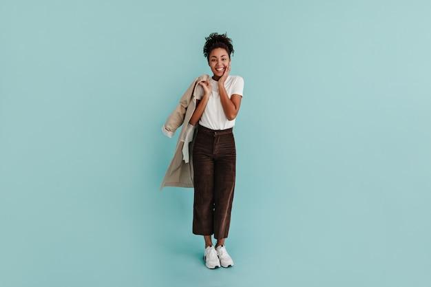 Mode jeune femme tenant un trench-coat