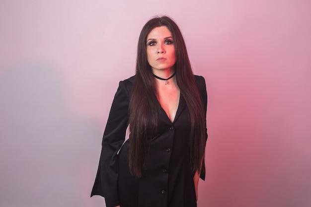 Mode jeune femme va à la fête d'halloween. costume de carnaval de sorcière. portrait de jeune fille sexy en robe noire