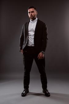 Mode jeune homme d'affaires avec une barbe dans un costume noir