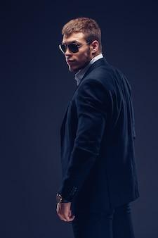 Mode jeune homme à lunettes de soleil, costume de luxe. vue arrière
