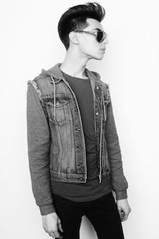Mode jeune homme avec des lunettes de soleil à la mode sur fond blanc