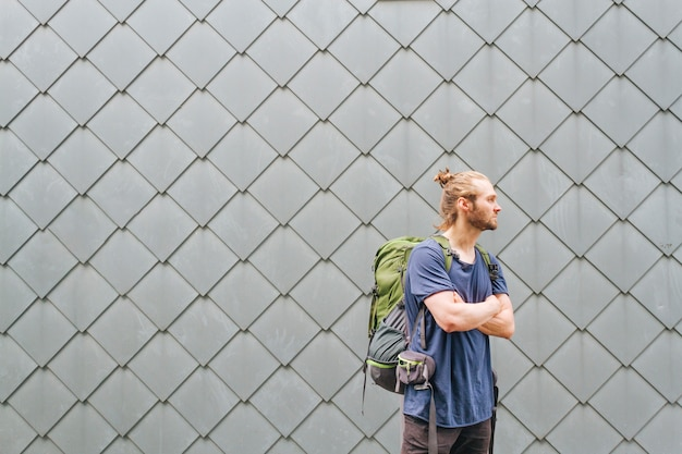 À la mode jeune homme avec sac à dos de voyage à la recherche de suite