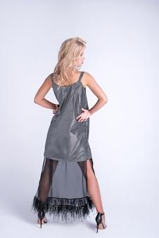 Mode jeunes femmes en robe tendance, maquillage. coiffure ondulée élégante, tenue noire. maquillage pose sur gris