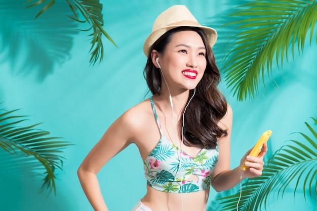 Mode jolie femme asiatique écoutant de la musique et souriant sur fond d'été lumineux