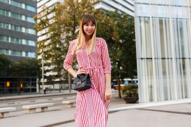Mode jolie femme en robe rouge posant dans la rue.