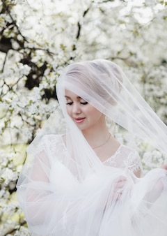 Mode mariée blonde en robe de mariée et voile de dentelle sur la nature. fille de beau modèle dans le jardin fleuri. portrait de femme dans le parc.