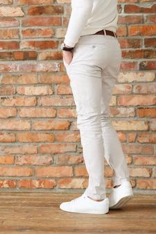 Mode masculine sur plancher en bois, jeune homme posant