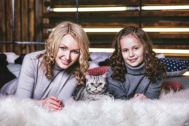 Mode mignonne petite fille et belle femme avec un chaton britannique dans les bras de très heureux ensemble