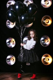 Mode mignonne petite fille avec un tas de ballons noirs contre le mur avec des lampes