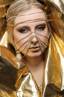 Mode moden vêtu de maquillage glamour dans des tons dorés.