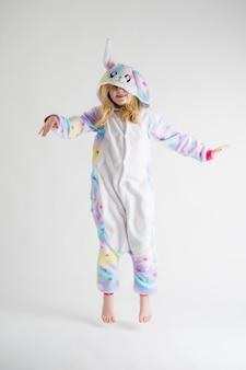 Mode moderne - belle fille blonde posant sur fond blanc en pyjama kigurumi, costume de lapin