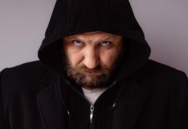 Mode portrait bel homme barbu élégant portant un manteau noir avec capuche