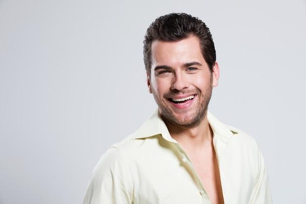 Mode portrait de bel homme heureux en chemise jaune pose