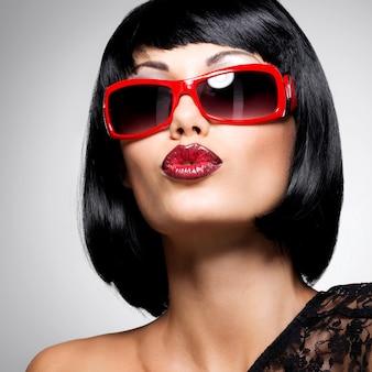 Mode portrait d'une belle femme brune avec une coiffure de tir avec des lunettes de soleil rouges