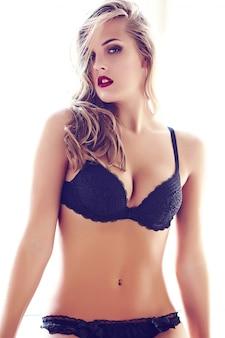 Mode portrait de la belle sexy jeune adulte blonde femme modèle portant de la lingerie érotique noire posant dans un intérieur clair le matin