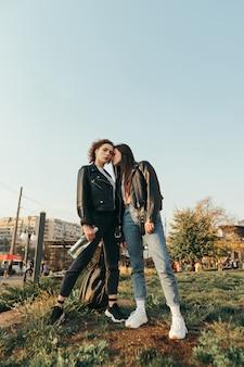 Mode portrait de deux filles en vêtements de rue debout sur l'herbe
