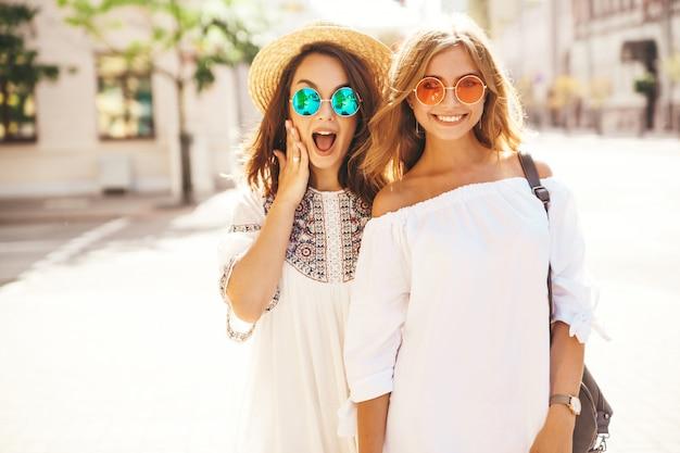 Mode portrait de deux jeunes femmes hippies élégantes brune et blonde. meilleurs amis en robe hipster d'été blanc posant
