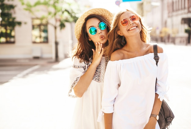 Mode portrait de deux jeunes femmes hippies élégantes brune et blonde modèles en journée ensoleillée d'été dans des vêtements hipster blanc posant. devenir fou