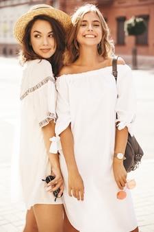 Mode portrait de deux jeunes femmes hippies élégantes brune et blonde modèles en journée ensoleillée d'été dans des vêtements hipster blanc posant. sans maquillage