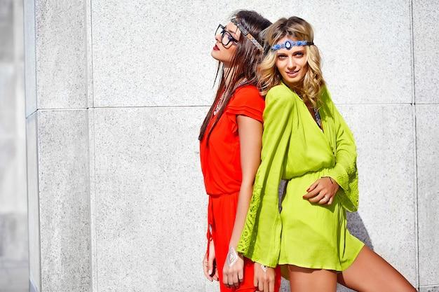 Mode portrait de deux jeunes femmes hippies modèles en journée ensoleillée d'été dans des vêtements hipster colorés lumineux