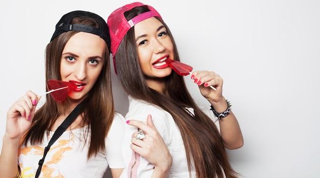 Mode portrait de deux jeunes filles jolies hipster portant un maquillage lumineux et tenant des bonbons.