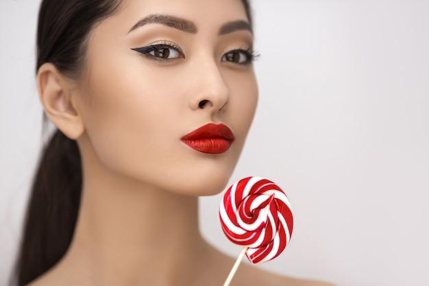 Mode portrait de femme asiatique avec sucette en studio