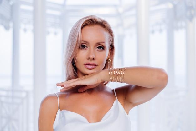 Mode portrait de femme blonde européenne en soie blanche robe romantique d'été bracelet doré et boucles d'oreilles