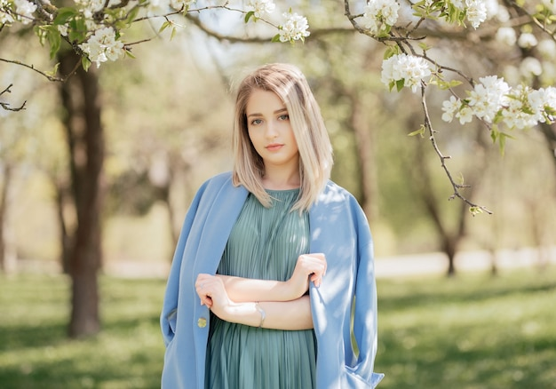 Mode portrait d'une femme blonde en robe verte et manteau bleu dans le parc du printemps