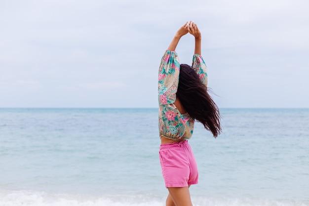 Mode portrait de femme élégante en haut à manches longues imprimé coloré et short rose sur la plage, fond tropical.
