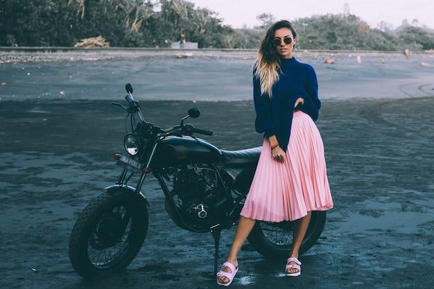 Mode portrait de femme élégante à lunettes de soleil, pull bleu et jupe rose, se dresse à vélo noir sur la plage de sable noir.