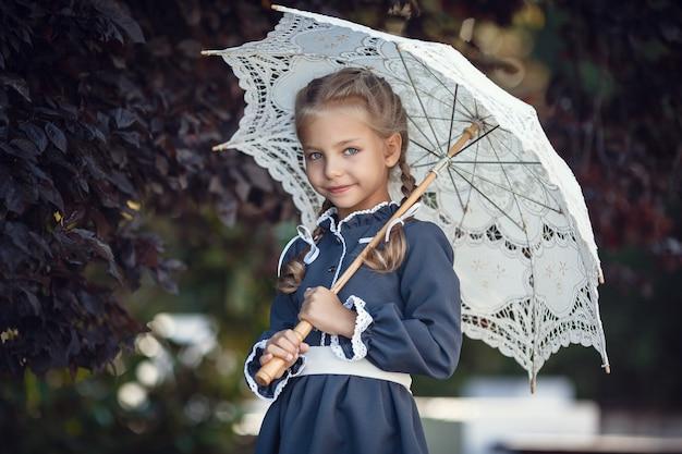 Mode portrait de femme de jeune fille assez branchée posant à la ville en europe, mode de rue de printemps. portrait riant et souriant. style rétro, imperméable et lèvres rouges