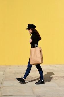 Mode portrait femme avec des sacs à provisions portant une tenue noire avec un chapeau posant sur un mur jaune.