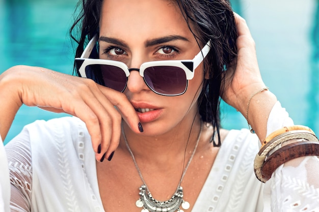 Mode portrait d'une femme sensuelle incroyable avec un corps bronzé parfait posant dans des lunettes de soleil à la mode dans la piscine
