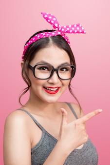Mode portrait d'une fille asiatique avec des lunettes de soleil debout sur fond rose.