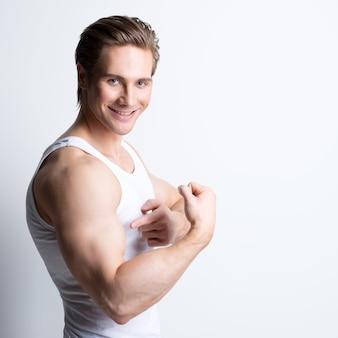 Mode portrait d'un homme souriant attrayant en chemise blanche pose sur le mur avec des ombres de contraste.