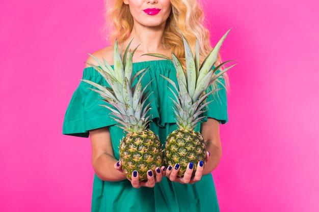 Mode portrait jeune belle femme à l'ananas sur un mur rose.