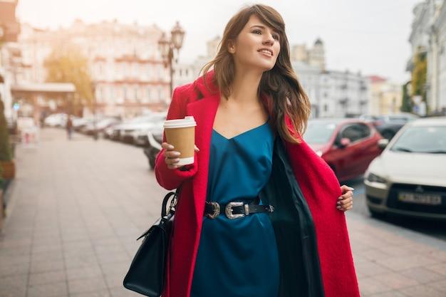 Mode portrait de jeune belle femme élégante marchant dans la rue de la ville en manteau rouge, tendance de style automne, boire du café, souriant, heureux, vêtu d'une robe en soie bleue