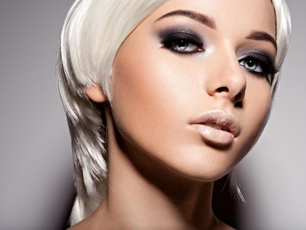 Mode portrait de jeune femme aux cheveux blonds et maquillage noir des yeux