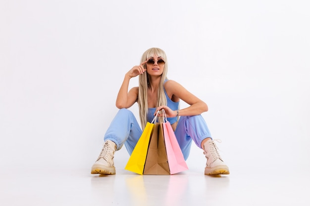Mode portrait de jeune femme blonde aux longs cheveux raides magnifiques avec des sacs colorés en studio sur un blanc.
