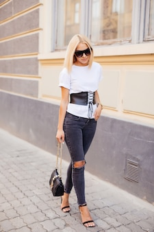 Mode portrait de jeune femme blonde élégante en plein air. robe grise, sac à dos en cuir, lunettes de soleil