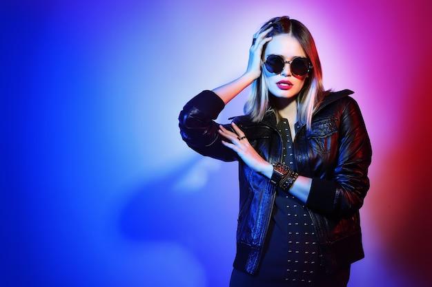 Mode portrait de jeune femme élégante à lunettes de soleil. veste en cuir noir, fond coloré, tourné en studio